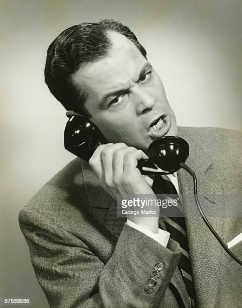 Businessman using phone in studio, (B&W), close-up