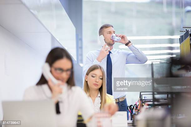 Businessman using phone while drinking water