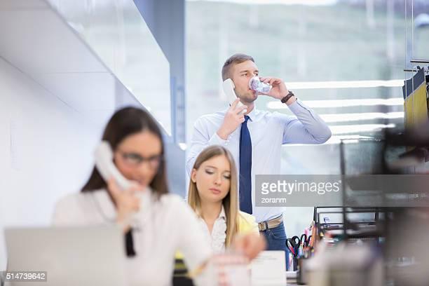 Geschäftsmann am Telefon, während sie trinkt Wasser