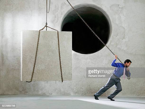 Businessman Using Pulley to Lift Cube Near Round Hole