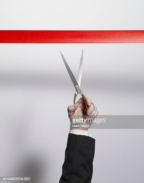 Businessman using scissors to cut red tape, close-up of arm