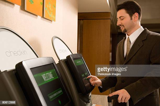 Businessman using self check-in terminal