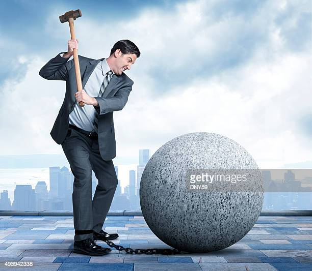 Businessman Using Sledgehammer To Break Free Of Ball And Chain