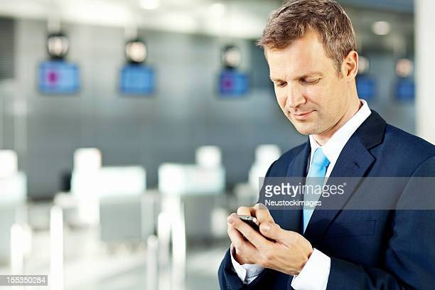 Uomo d'affari utilizzando Smart Phone in aeroporto