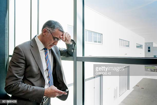 Businessman using smartphone by glass wall