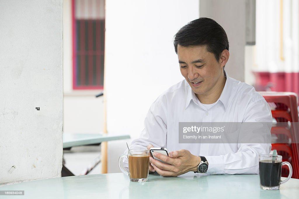 Businessman using smartphone in local coffeeshop : Stock Photo
