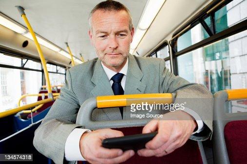 Businessman using smartphone on bus : Stock Photo