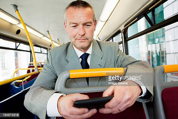 Businessman using smartphone on bus