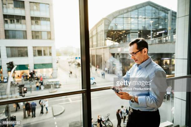 Businessman Using Smartphone Standing By Window In Hotel Room
