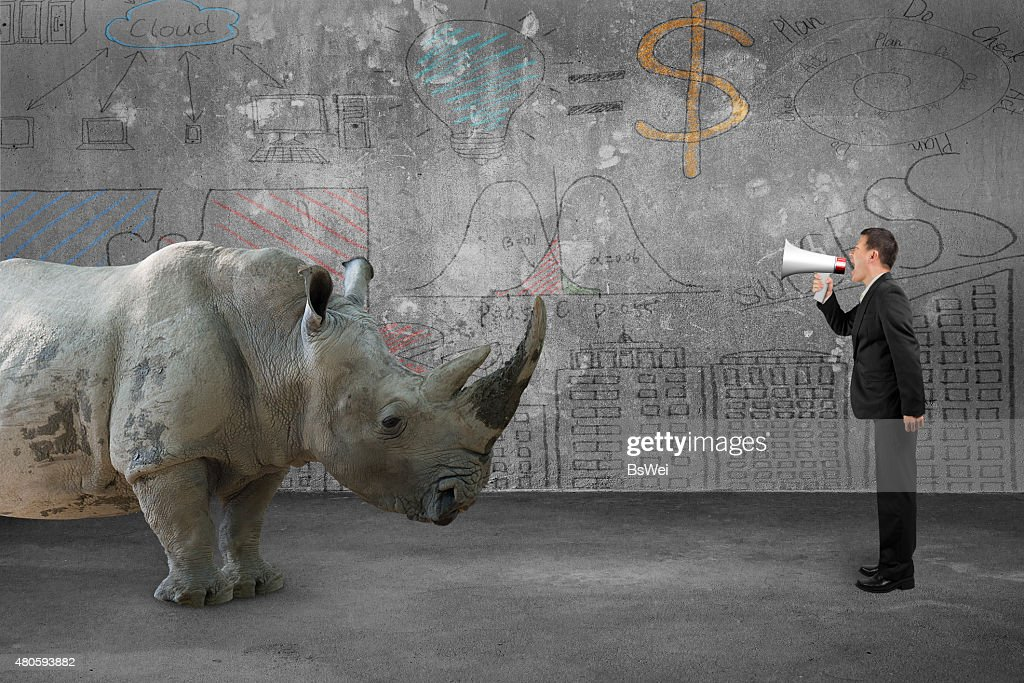Businessman using speaker against rhinoceros with doodles wall : Stock Photo