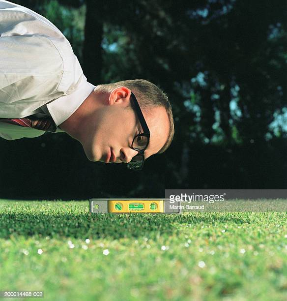 Businessman using spirit level on lawn, close-up
