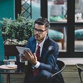 Businessman using tablet at cafe