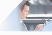 Businessman using tablet computer in backseat of car