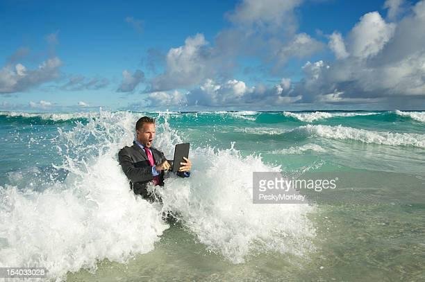 Businessman Using Tablet Computer in Crashing Waves Sea