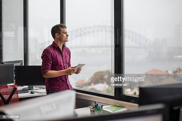タブレットコンピューターを使用して実業家のオフィス