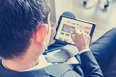 Businessman using tablet computer while sitting on the couch, over shoulder view, blurred screen - vintage tone
