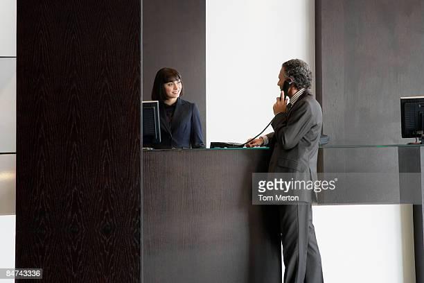 Businessman using telephone at reception desk