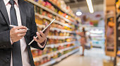 Businessman using the tablet and writing the order stock on Supermarket blur background, business technology concept