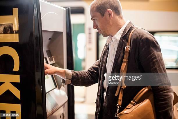 Businessman using ticket machine at railway station