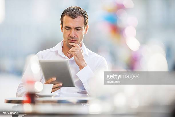 Businessman using touchpad outdoors.