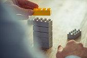 Businessman staking toy building blocks