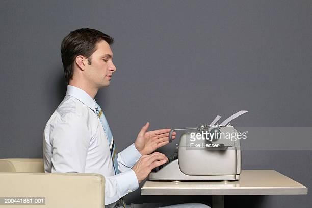 Businessman using typewriter, side view