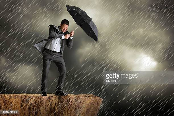 Businessman using umbrella for protection against driving rain