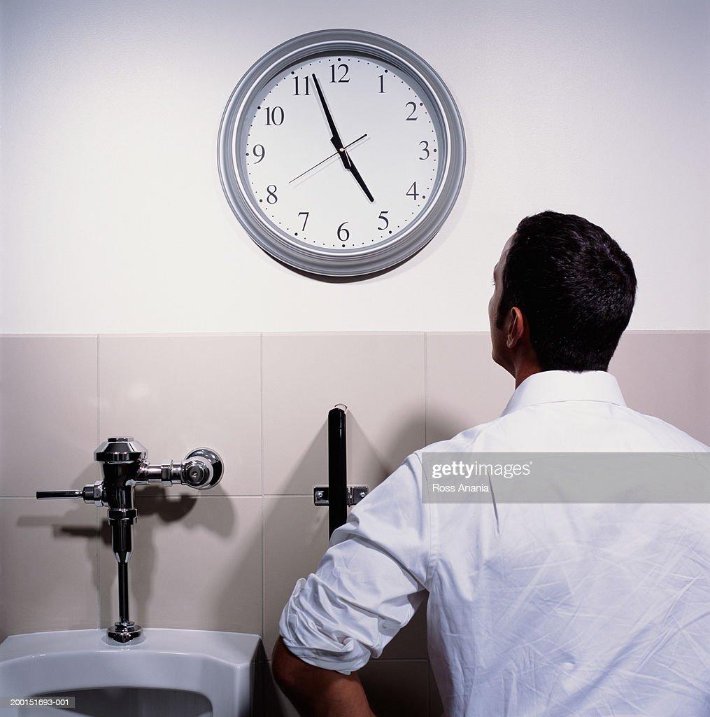 Businessman using urinal, looking up at wall clock, rear view