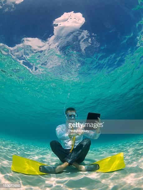 Homme d'affaires à l'aide de tablette numérique imperméable sous l'eau dans la mer Tropical