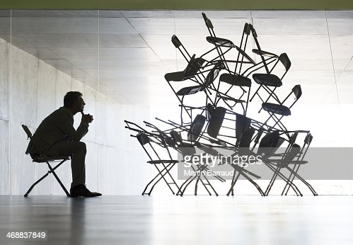 Businessman viewing office chair installation art