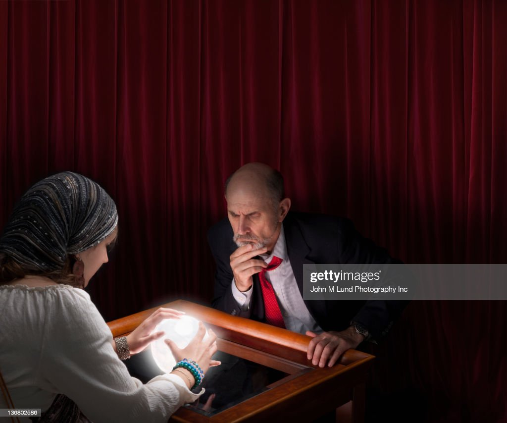 Businessman visiting fortune teller with crystal ball : Stock Photo