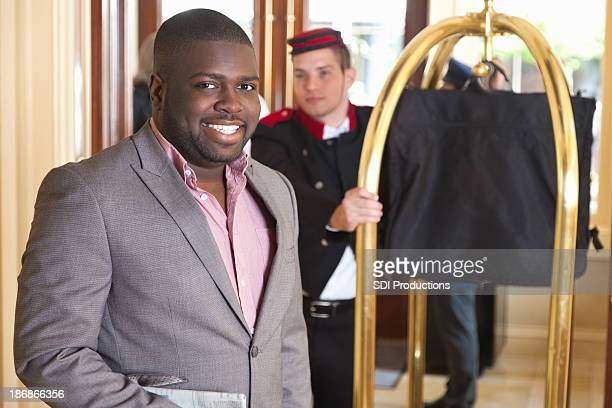 Businessman waiting for bellhop with luggage at hotel entrance