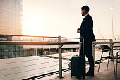 Shot of young businessman standing on airport lounge balcony with suitcase and looking outside. Man waiting for his flight in airport terminal.