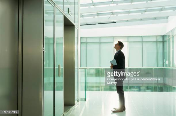 Businessman waiting for lift in office
