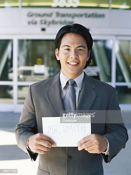 Businessman waiting in airport holding sign, portrait