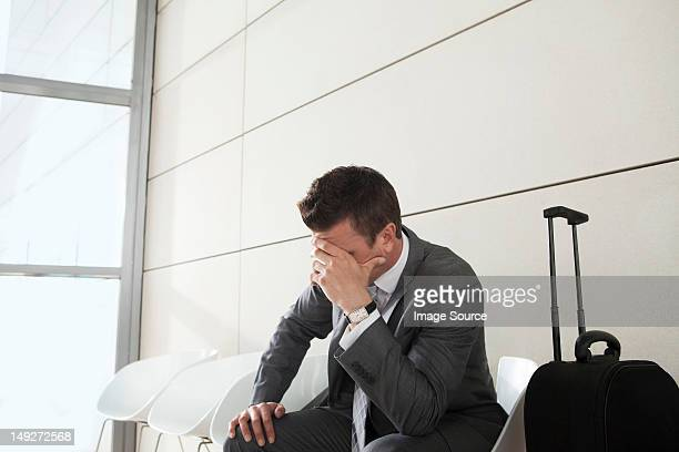 Businessman waiting with luggage, head in hands