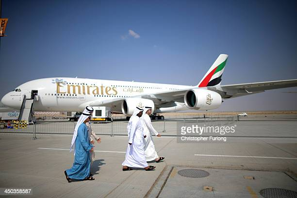 Businessman walk past an Emirates Airbus A380 during the Dubai Airshow on November 18 2013 in Dubai United Arab Emirates The Dubai Air Show is the...