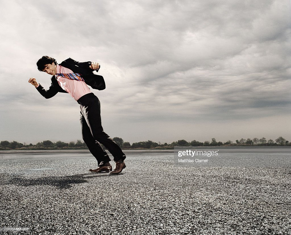 Businessman walking against strong wind : Stock Photo