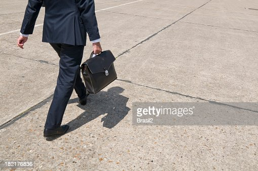 A businessman walking along a concrete floor