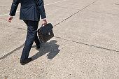 A businessman walking along a concrete floor