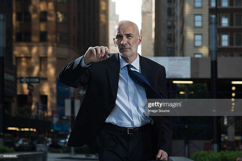 Businessman walking along a street : Stock Photo