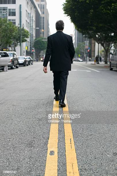 Businessman walking along dividing line on a city street
