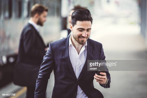 Businessman Walking Along Train Station Platform