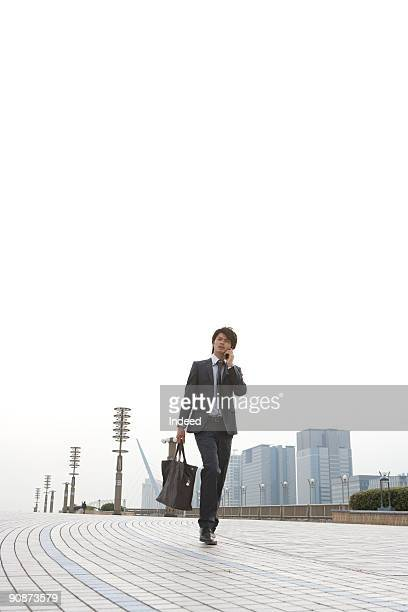 Businessman walking and using mobile phone