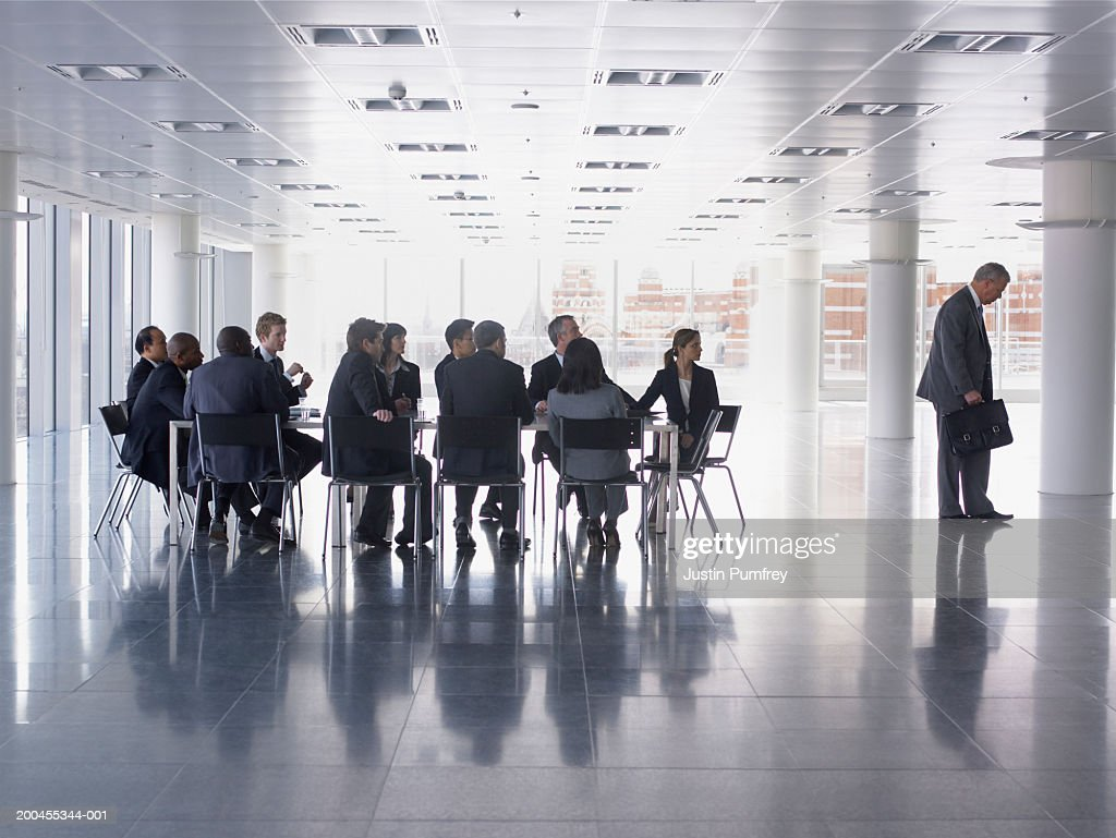Businessman walking away from colleagues with head bowed : Stock Photo