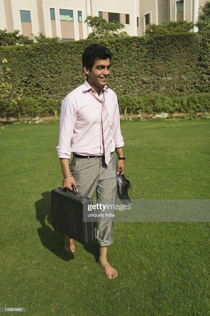 Businessman walking barefoot in a park, Gurgaon, Haryana, India : Stock Photo