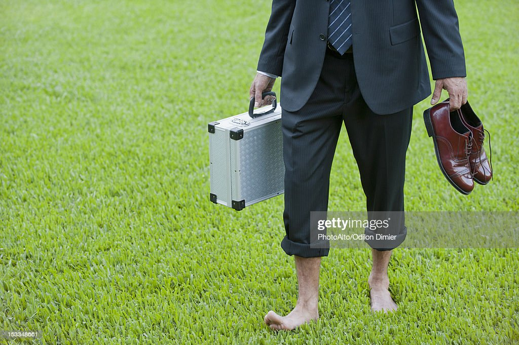 Businessman walking barefoot on grass carrying shoes and briefcase