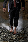 Businessman walking barefoot over hot coals, mid section
