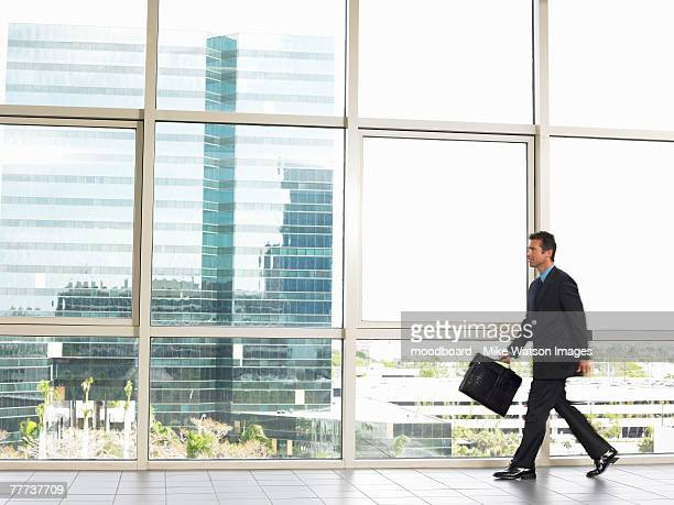 Businessman Walking by Window