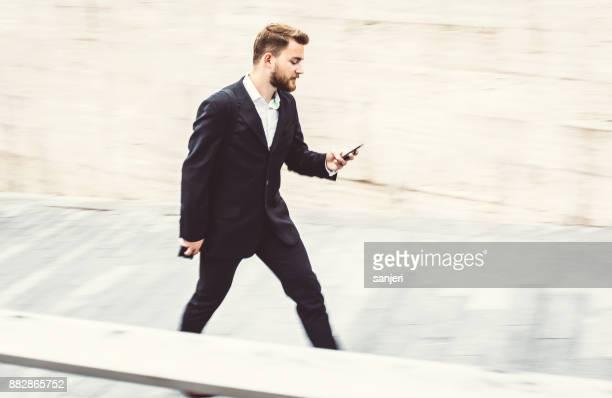 実業家ウォーキング、携帯電話をチェック